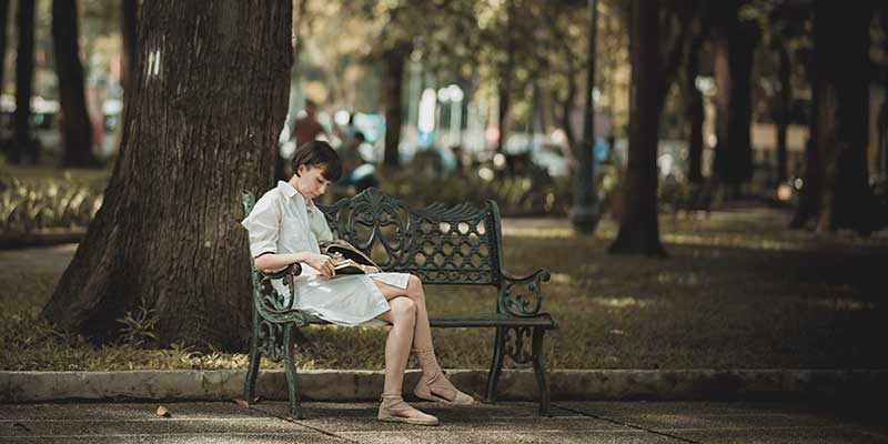 woman reading on a park bench